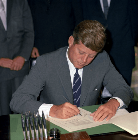 Kennedy signing the Maternal and Child health and Mental Retardation Planning Bill; 'gift pens' on the desk